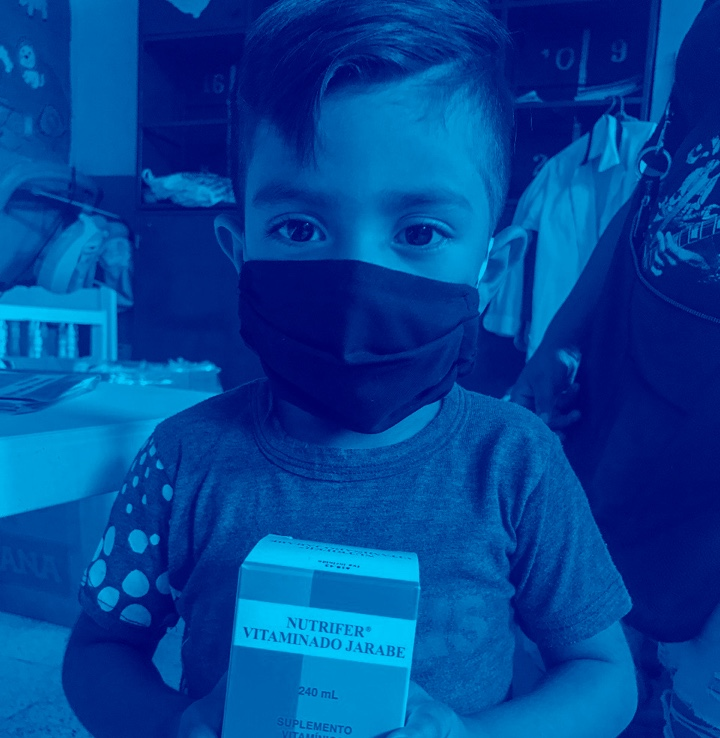 Young boy holds a box of vitamins while wearing a black facemask.