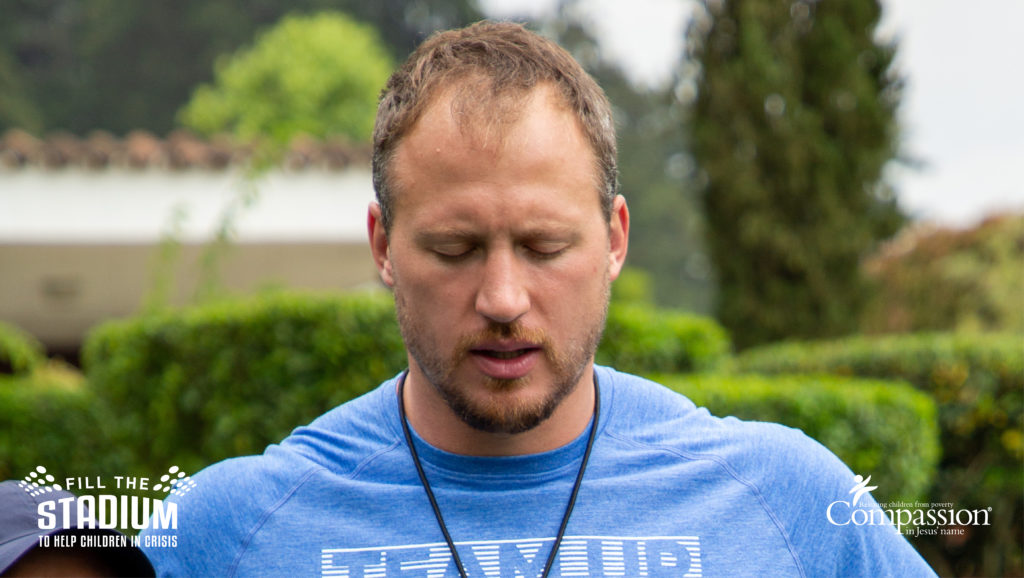 Nate Solder bows his head in prayer while standing outside.